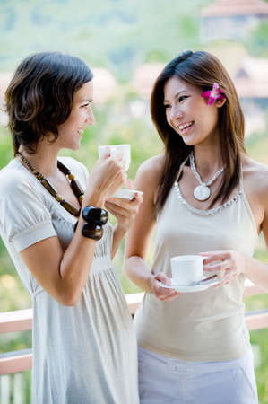 Two attractive young women catching up over coffee outside