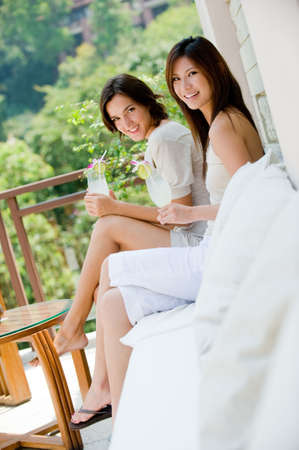 Two attractive young women sitting on a sofa outside with tropical drinks photo