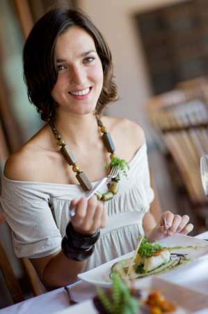 A young attractive woman eating a meal at a table outdoors Stock Photo