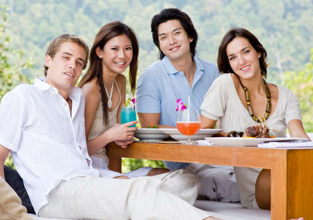 A group of four young adults sitting together to enjoy a meal with drinks outdoors photo