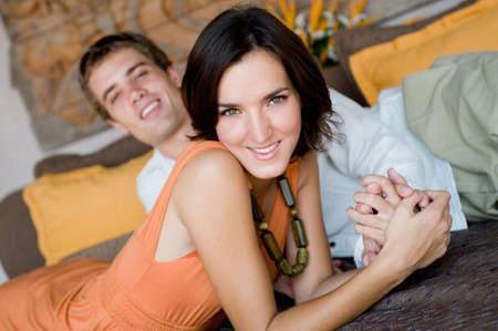 couple au lit: Un jeune couple en vacances attrayant allong� sur un daybed