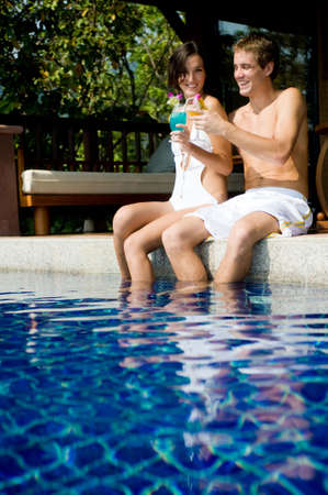 A young attractive couple sitting poolside with tropical cocktails Stock Photo - 2634965