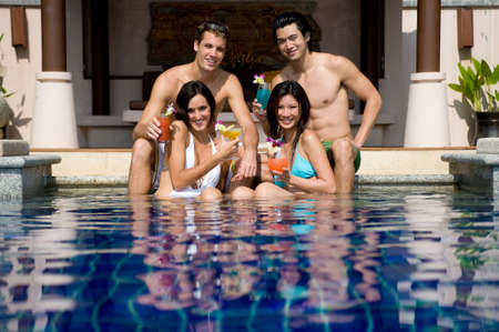 Four young adults sitting in a pool with tropical cocktails photo
