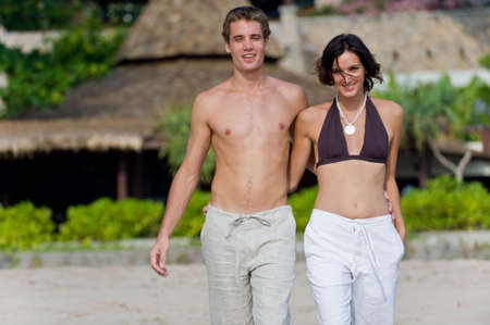 A young attractive couple walking arm in arm on beach with resort behind them photo