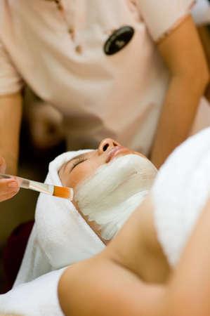 A young woman has a facial treatment at a spa