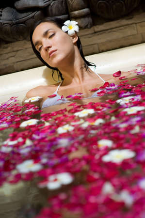 A young woman relaxing in an outdoor bath filled with flowers and petals