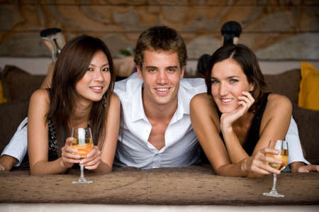 threesome: Three young adults lying on a daybed with glasses of wine