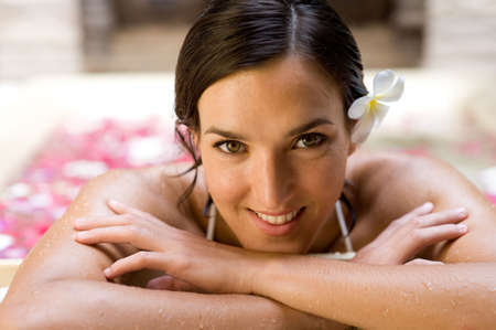 A beautiful young woman in a bath of flowers at a spa Stock Photo - 2645720