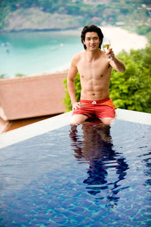 sittting: A young Chinese guy in pool with beach behind