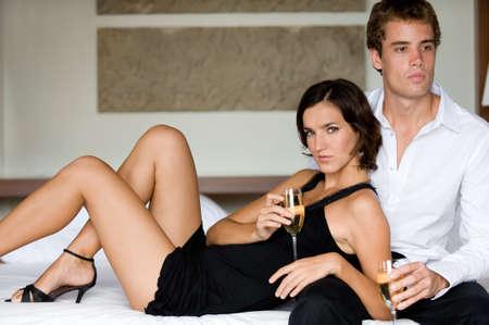 luna de miel: Un par joven con champ�n en la cama