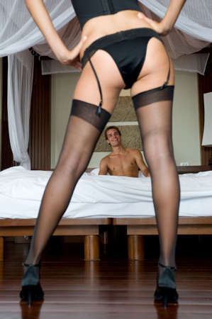 A sexy woman in lingerie standing in front of a man in bed