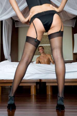 ropa interior femenina: Una sexy mujer en ropa interior de pie delante de un hombre en la cama  Foto de archivo