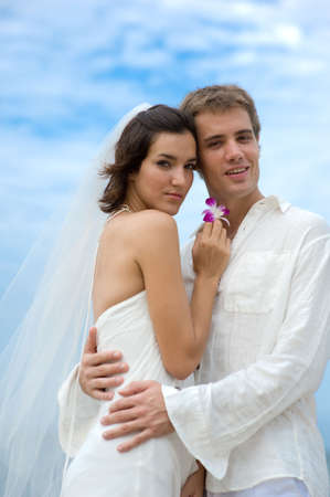 A young bride and groom standing together on a beach photo