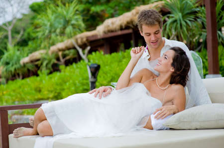 A young bride and groom lying together in an outdoor setting by beach