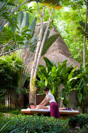 A young woman getting a massage in a tropical spa