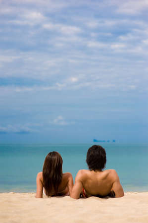 A couple sitting on the beach in front of the ocean Stock Photo - 2651175
