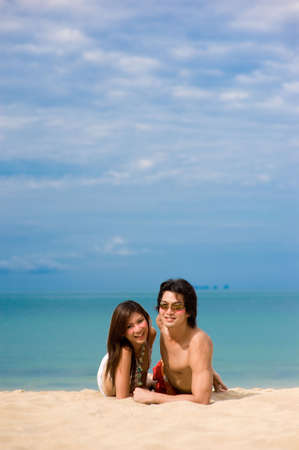 A young Asian couple sitting on beach with ocean behind photo