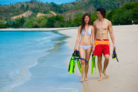 A young couple with snorkelling gear on a tropical beach Stock Photo - 2651250