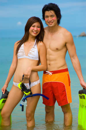 A young couple with snorkelling gear on a tropical beach Stock Photo - 2651241