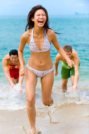 A young woman is being splashed at the beach by two male friends photo