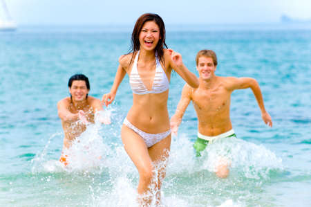Two young men splashing their sexy female friend in blue sea