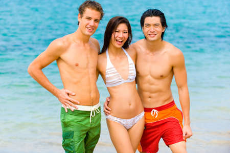 Three friends standing by the ocean photo