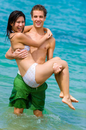 A young man holding his girlfriend whilst standing in the sea Stock Photo - 2651253
