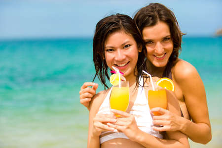 Two attractive young women drinking cocktails on beach photo