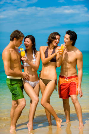 Four young adults standing by ocean with drinks photo