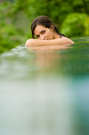 A young woman relaxing in a swimming pool Stock Photo - 2668409