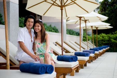 A young couple relaxing together on a lounger by pool photo