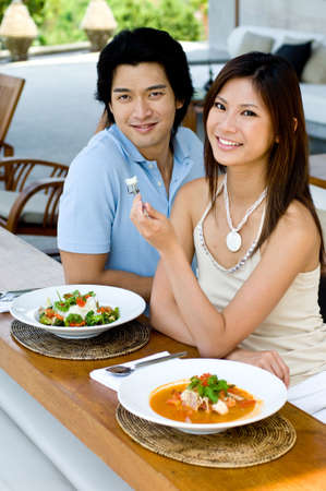pareja comiendo: Un par atractivo joven que come el alimento tailand�s Foto de archivo