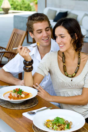 A young couple on vacation eating lunch at a relaxed outdoor restaurant