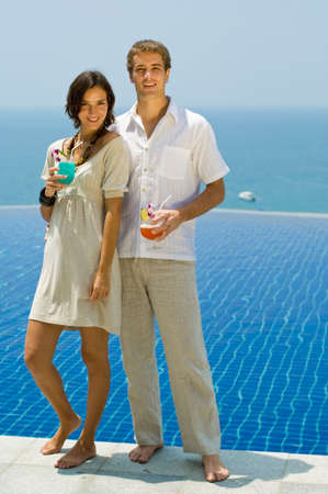 A stylish young couple with cocktails by the pool photo