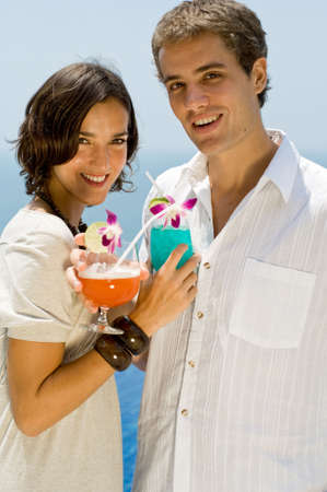 A young couple holding cocktails on vacation photo