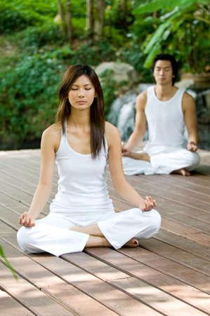 A young couple doing yoga outside photo