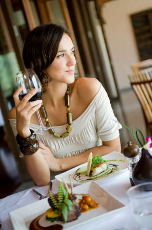 A young woman enjoying a meal and wine Stock Photo