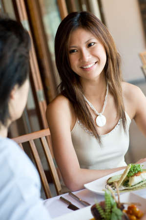 sophisticated: A young woman enjoying a meal at outdoor restaurant