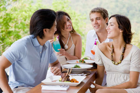 Four young adults enjoying a meal together on vacation Stock Photo