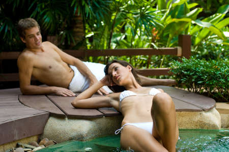 A young attractive couple lying by a pool in tropical setting photo