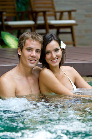 A young attractive couple in a pool in tropical setting photo