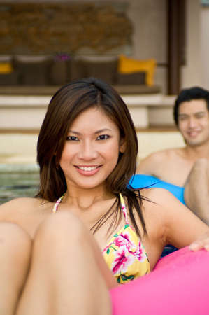 A young couple sitting in rubber rings in swimming pool photo