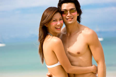 A young Asian couple on beach with ocean behind photo