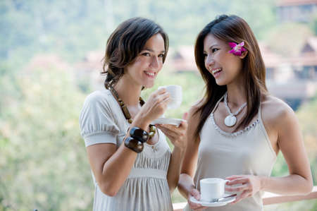 Two young women together outside having coffee Stock Photo