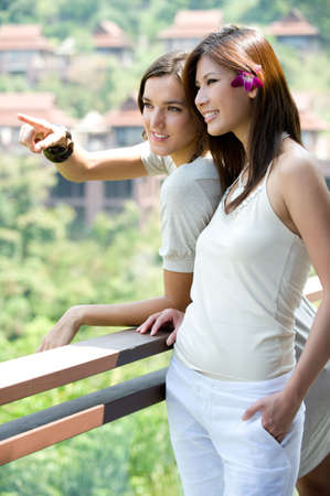 Two attractive young women standing on balcony looking at view Stock Photo - 2725513