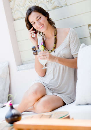A young woman on vacation, holding a cocktail and making a phone call on a mobile phone photo