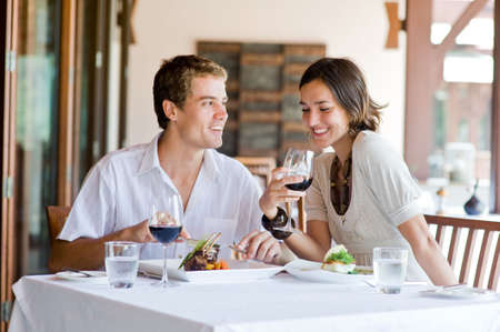 A young couple sitting at a table at an outdoor restaurant Stock Photo