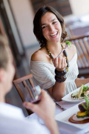 outdoor eating: A young woman laughing whilst eating dinner at a restaurant