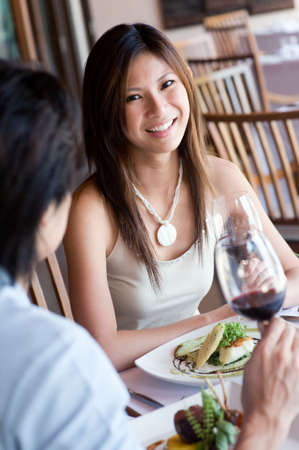 woman eat: A young woman smiling whilst eating dinner at a restaurant
