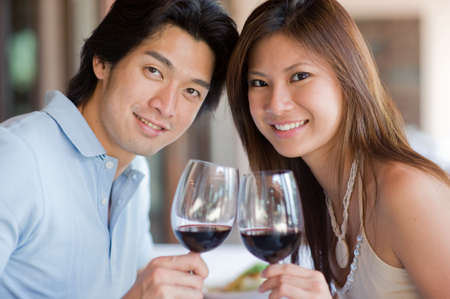 A young couple with red wine at a restaurant photo